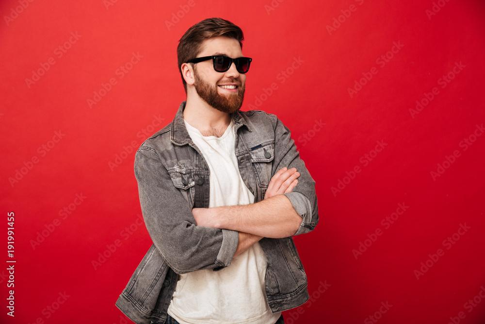 Wizerunek mody młody człowiek jest ubranym okulary przeciwsłonecznych i drelichowy ono uśmiecha się i pozuje z rękami składać, odizolowywający nad czerwonym tłem <span>plik: #191991455 | autor: Drobot Dean</span>
