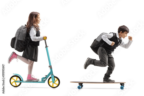 Full length profile shot of a schoolgirl riding a scooter and a schoolboy riding Canvas Print