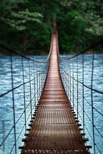 Suspension bridge. Landscape view of Long Steel Suspension bridge above the river. balance