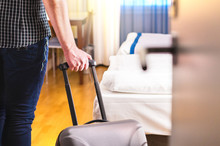 Man Pulling Suitcase And Enter...
