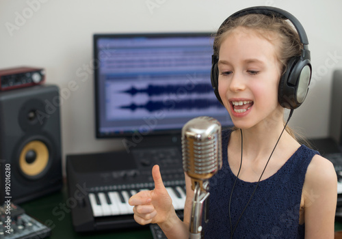 Láminas  Little girl singing a song in home recording studio.