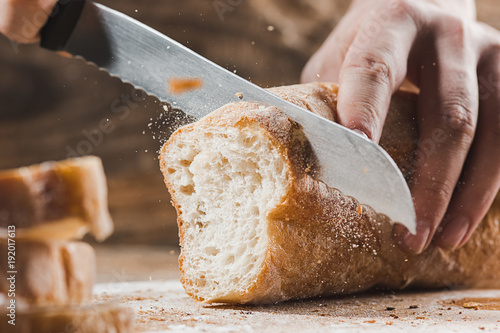 Poster Brood Whole grain bread put on kitchen wood plate with a chef holding gold knife for cut.