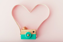 Toy Camera With Heart Shaped Strap On Pink Background