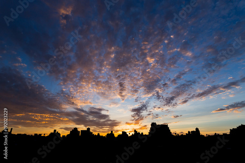 Sunset over rooftops and water towers in a city