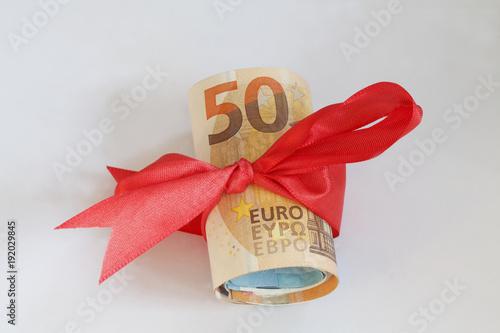 Fotografía  Geldrolle, Fünzig Euroscheine mit roter Schleife als Geschenk
