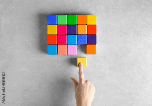 Fotografie, Tablou Woman with color cubes on light background. Unity concept