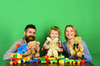 Parents and kid in playroom. Family with happy faces