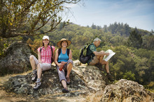 Hikers Resting On Rocks And Reading Map