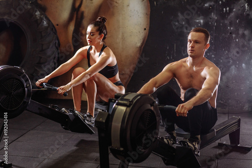 Autocollant pour porte Fitness Athletic couple training on row machine at cross gym