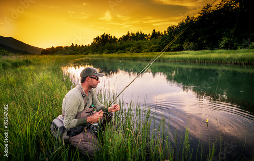 Foto op Canvas Vissen Fly fisherman fishing pike in river