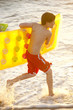 Caucasian boy running into ocean carrying inflatable raft