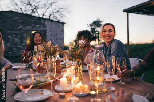 Millennials enjoying dinner in outdoor restaurant Wallpaper Mural