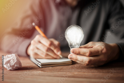 Photo  Businessman holding light bulb and writing down in the notebook new creative ideas