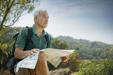 Caucasian Man Hiking And Reading Map