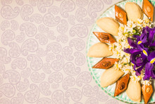 Novruz Celebration Plate With Traditional National Pastries In Azerbaijan Shekerbura And Pakhlava Decorated With Spring  Flowers Daffodils And Purple Fleur De Lis Silk Light Grey Background Copy Space