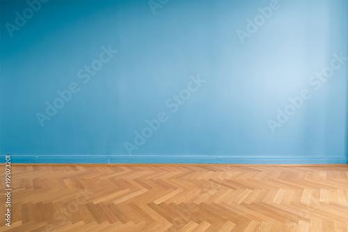 Obraz blue wall  in empty room with parquet floor - fototapety do salonu