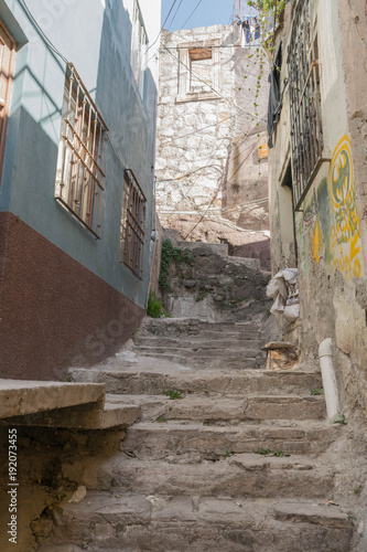 Poster Smal steegje Steep and narrow stone stair passageway, with decaying stone walls with graffiti, and other architectural elements, in Guanajuato, Mexico