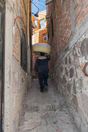 Spoed Foto op Canvas Smal steegje From the back, a man with a basket of laundry on his head, walking up a narrow stone pathway, between two stone walls, in Guanajuato, Mexico