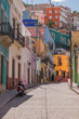 A hilly cobblestone street with many colorful houses and one scooter, parked, in Guanajuato, Mexico
