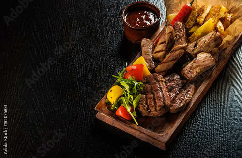 Photo Stands Meat Assorted delicious grilled meat with vegetable. Mixed grilled bbq meat with vegetables. Mixed grilled meat on wooden platter