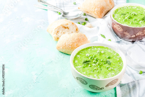 Green pea soup with fresh bread on light blue concrete table, copy space