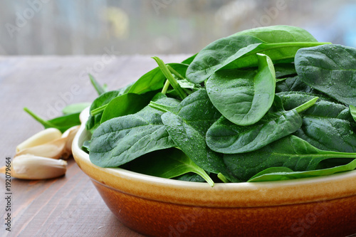 Baby spinach leaves in stoneware bowl on wooden table