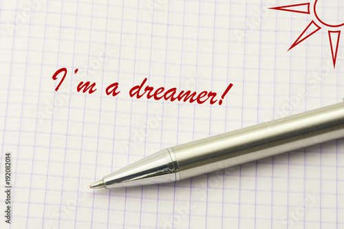 dreamer word written on paper dreaming textual concept with sun and silver pen