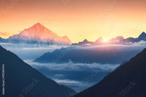 Foto auf AluDibond Gebirge Majestic scene of silhouettes of mountains and low clouds at colorful sunrise in Nepal. Landscape with snowy peaks of mountains, beautiful sky and yellow sunlight. Rocks and sun rays.Nature background