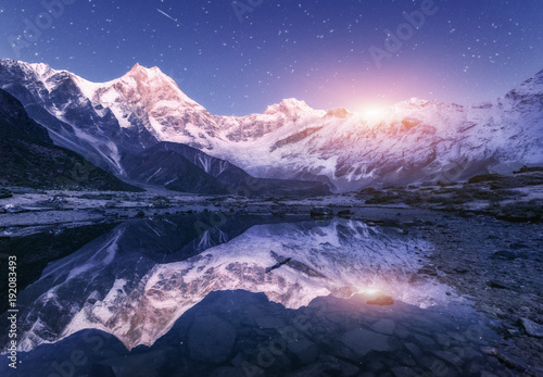 Foto auf AluDibond Reflexion Night scene with himalayan mountains and mountain lake at starry night in Nepal. Landscape with high rocks with snowy peak and sky with stars and moon reflected in water. Moonrise Beautiful Manaslu