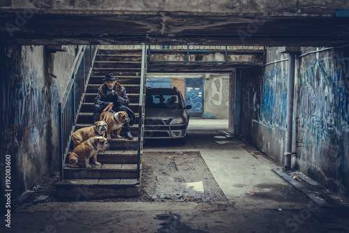 Canvas Prints Light pink Man sitting on the stairs and holding three English bulldogs