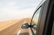 Car mirror, road and yellow desert around in a summer