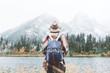 Leinwandbild Motiv Styish woman feeling happy among amazing mountains, enjoy the nature landsape. Forest and lake, wearing backpack, hat and poncho, boho and wanderlust style
