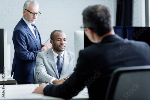 Fototapety, obrazy: partial view of multicultural businessmen working together in office