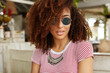 Headshot of fashionable African American female with bushy curly hairstyle, wears stylish sunglasses, has vacations in luxury hotel, comes to cafe have dinner, waits for order, enjoys good service