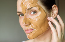 Girl Puts On A Mask Of Red Clay