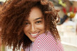 Glad cheerful African American female model with frizzy dark bushy hair, being in high spirit after hearing good news or recieving compliment from boyfriend, poses at camera with gentle smile.