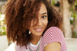 Close up shot of lovely dark skinned mixed race female with wavy dark hair, smiles pleasantly, wears striped t shirt, being satisfied with everything. Adorable African woman expresses happiness