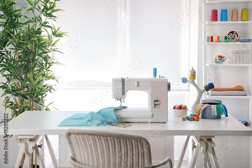 Foto  Sewing machine with fabric on table in tailor workshop