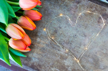 View Of Colorful Orange Tulips And Led Lights Chain Shaped In Heart Form On Old Rustic Vintage Wooden Background. Love, Valentines Or Mother's Day Background