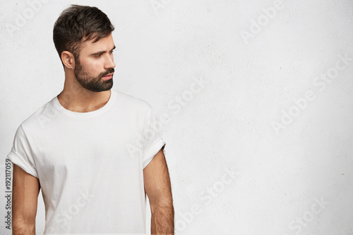 Fotografia Bearded serious male in white t shirt, poses against white blank copy space for your advertisment or promotional text