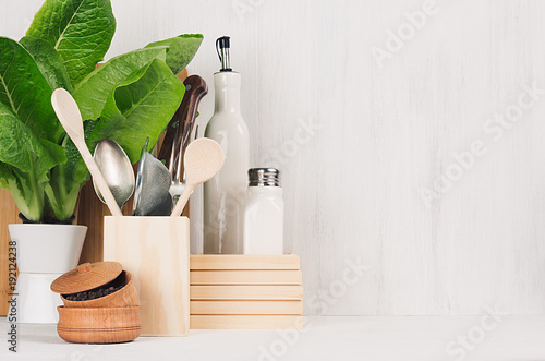 Photo  Kitchen white interior with wooden beige kitchenware, spices, ceramics and green spinach bush on light wood board, copy space