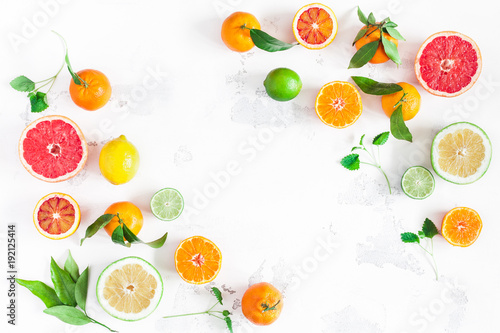 Poster Fruit Fruit background. Colorful fresh fruits on white table. Orange, tangerine, lime, lemon, grapefruit. Flat lay, top view, copy space