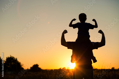 Father and son playing in the park at the sunset time.
