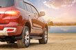 Rear-wheel drive SUV red cars mountains and sky background.