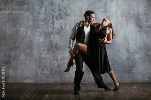 Poster Dance School Young pretty woman in black dress and man dance tango