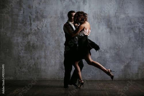 Photo Young pretty woman in black dress and man dance tango