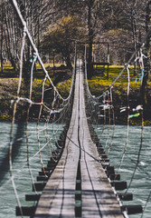 FototapetaBeginning of an adventure, road into the jungle. Suspension bridge. Landscape view of Long Steel Suspension bridge above the river. balance