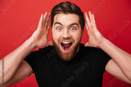 Portrait close up of excited stylish man wearing black t-shirt screaming in surp Fototapeta