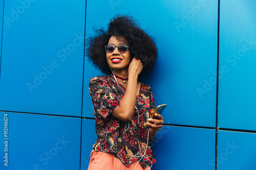 Poster Magasin de musique Beautiful glad african girl in colorful clothes and sunglasses listening to music in earphones on her cell phone. Standing against the wall, outdoors.