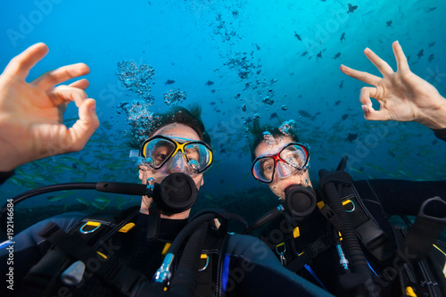 Couple of scuba divers showing ok sign, portrait photography